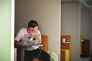 a coder, judging by the pictures on his laptop, remains intently focused on his computer screen, looking a bit frustrated